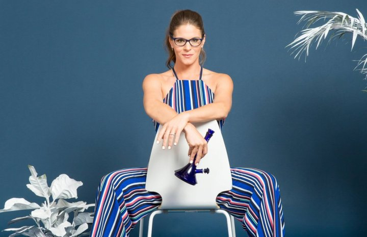 Jane West sitting on a white chair with blue glass bong